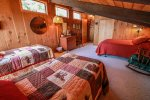 The sleeping loft area features a full bed and two twin beds.