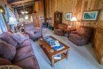 The cozy living space features a living room, dining area, and kitchen, plus a wood burning stove.