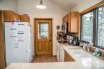 The kitchen features full sized appliances, including a dishwasher, and granite counters.