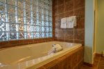 Bathroom features a nice jetted tub and shower.