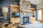 The living room features a beautiful stone-surround gas fireplace and TV.