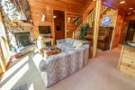 The living room is spacious and open with traditional log cabin decor.