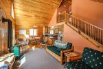 The open living area feels spacious and inviting with vaulted ceilings and log cabin comforts.
