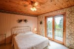 The master bedroom on the upper level has a queen bed and walk-out balcony with Lake Superior views.