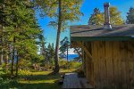 This quaint one-room cabin is nestled among mature trees with private Lake Superior shoreline nearby.