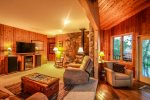 Wood panel walls and the stone fireplace surround add to the cabin feeling of this home.