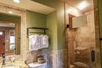 The beautiful tiled bathroom has a walk-in shower with seamless glass door.