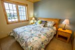 The guest bedroom has a queen size bed and views of the town of Grand Marais.