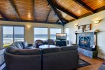 The living room offers comfortable furniture, a cozy fireplace and amazing views