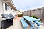 The back yard is fenced in, has a high-end Weber grill and picnic table with access to the rooftop deck.