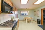 The kitchen offers access to the garage, dining room, and has a peak window into the den