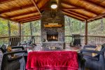 Outdoor deck with stone fireplace and plenty of seating