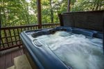 Hot tub on lower deck with seasonal views.