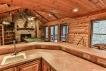 Upper level den with wet bar, pool table and custom stone wood burning fireplace