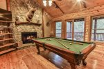 Den with pool table, custom stone wood burning fireplace TV