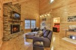 Great room with 60 inch TV mounted above the custom stacked stone wood burning fireplace