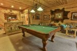 Terrace level game room with pool table, 32 inch TV, wet bar, and lounging area.
