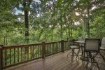 Deck dining surrounded in lush forest
