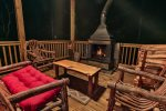 Cozy seating for four on main level deck by wood burning fireplace