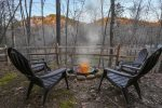 Fire pit in small fenced in area with river views