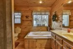 Upper level private bathroom with walk-in shower and jetted tub