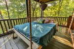 Swinging bed on the screened in porch with nature sounds