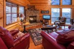 Greatroom with a flat screen tv, gas log fireplace and lots of windows