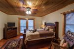 Queen bedroom upstairs with a flat screen tv and a private deck area overlooking the mountain tops