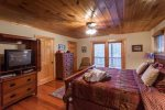 King Master bedroom on the main level with a TV and private deck access
