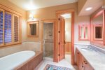 Master bathroom with soaking tub, walk-in shower, and separate toilet