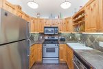 Fully-equipped kitchen with stainless steel appliances and slate counter tops