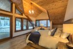 Master bedroom with a king-sized bed and vaulted ceilings