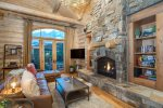 Enjoy the beautiful living space with a gas fireplace, flatscreen TV, built-in shelves, and deck access