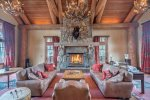 Stately great room with high ceilings and statement-making wood burning stone fireplace
