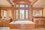 A giant soaking tub is flanked by a double vanity sink
