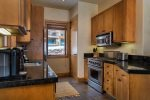 The fully-equipped kitchen has a gas range and high-end, stainless steel appliances