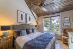 Sunny master bedroom with loft area above that includes a queen-sized bed