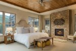 Huge master bedroom with king-sized bed and a gas fireplace
