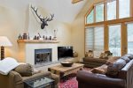 Comfortable living area with a gas fireplace flatscreen TV, and tons of natural light