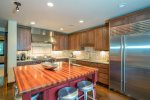 Large kitchen with high-end stainless steel appliances and an island with breakfast bar seating