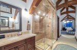 En suite master bathroom with a soaking tub and steam shower
