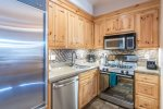 Stainless steel appliances and a fully-stocked kitchen await