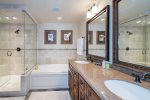 Master bathroom with double vanity, soaking tub, and walk-in shower
