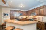 An open kitchen with stainless steel appliances and breakfast bar seating