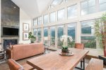 A huge panel of windows perfectly frames the mountains beyond
