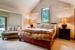The master bedroom has a king-sized bed and vaulted ceilings