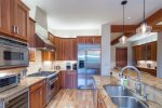 A fully-equipped kitchen complete with stainless steel appliances, granite countertops, and custom light fixtures