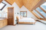 Master bedroom upstairs with a king-sized bed and vaulted ceilings