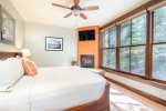 The king-sized master bedroom is brightly lit and has its own gas fireplace