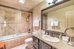 En suite master bathroom with a tub and shower combo and granite counters